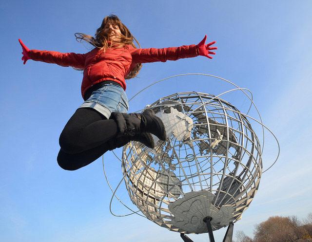 Saltando sobre la bola del mundo del parque de Queens